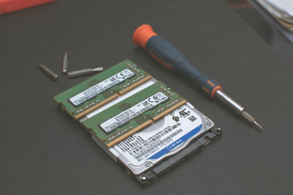 2 zielone kości pamięci RAM, dysk HDD, pomarańczowo-czarny wkrętak i 3 bity