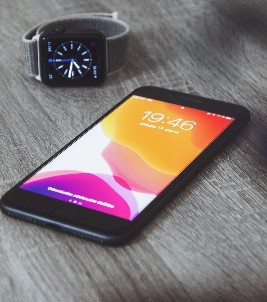 Czarny iPhone i czarny Apple Watch z srebrną bransoletą na szarym blacie biurka