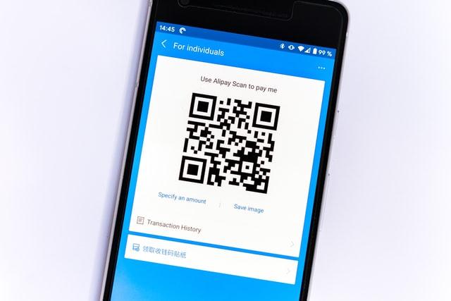 Czarny telefon z QR Code na biało-niebieskim tle