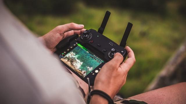 Mężczyzna steruje dronem za pomocą pilota i aplikacji