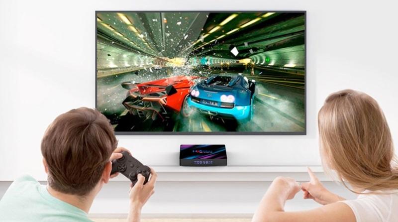Jak zrobić smart tv - gamepad do smart tv - para siedzi na kanapie i gra w grę