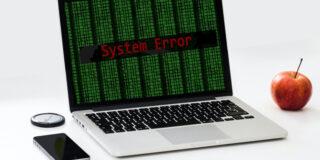 "Srebrny laptop z komunikatem ""System Error"""